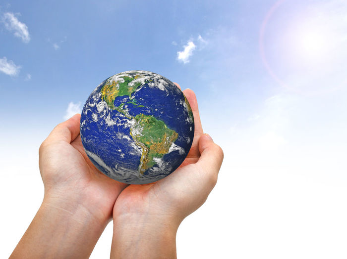 Close-up of hand holding planet earth against sky