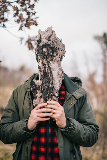 Man covering face with wood while standing in forest