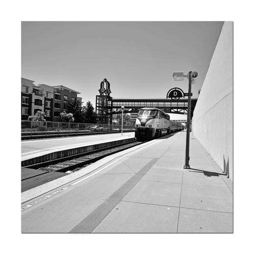 Train Platform 2 C.L. Dellums Amtrak Station Okj Est. 1995 Port Of Oakland,Ca. Jack London Square Platform & Track Amtak Train Locomotive Passengers Boarding All Aboard Pedestrian Crossing Overpass Rail Transportation Railroad_Photography Monochrome_Photography Monochrome Black & White Black & White Photography Black And White Black And White Collection  Shadows Lightpost Announcement Speaker Fence Condominium Architecture Train Sky Railroad Station Platform Passenger Train