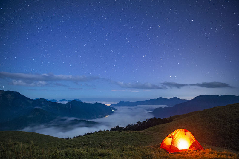 Tent on field against mountain range at night