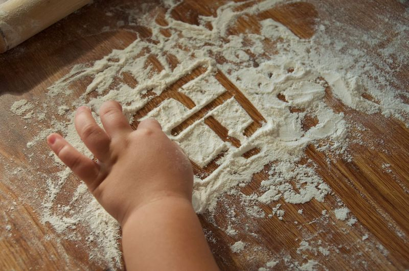 Cropped Hands Of Girl Playing With Flour On Table