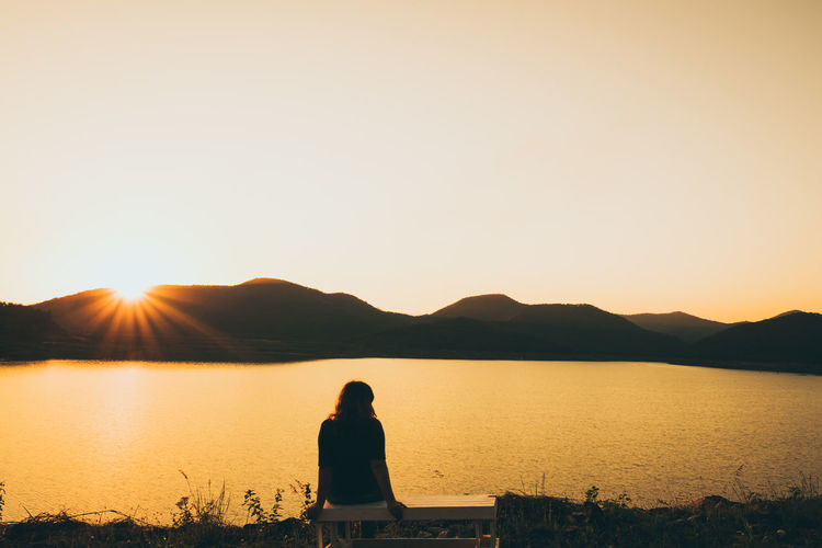 love nature Beauty In Nature Clear Sky Lake Leisure Activity Lifestyles Mountain Nature One Person Orange Color Outdoors Real People Rear View Relaxation Scenics Silhouette Sitting Sky Standing Sun Sunlight Sunset Tranquil Scene Tranquility Water Women