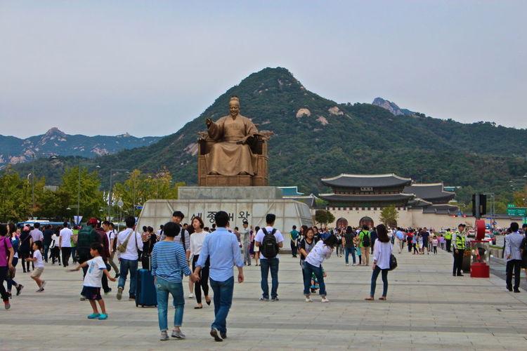 Crowd visiting statue of king sejong by gyeongbokgung against sky