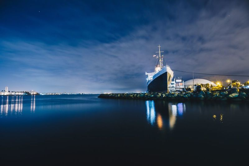 Commercial dock by sea against sky at night