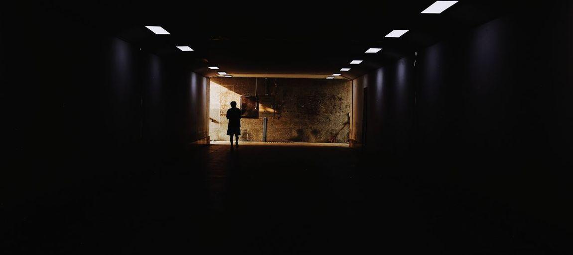 Silhouette man walking in corridor of building