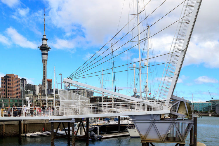 View of drawbridge at harbour against  cloudy sky and auckland sky tower