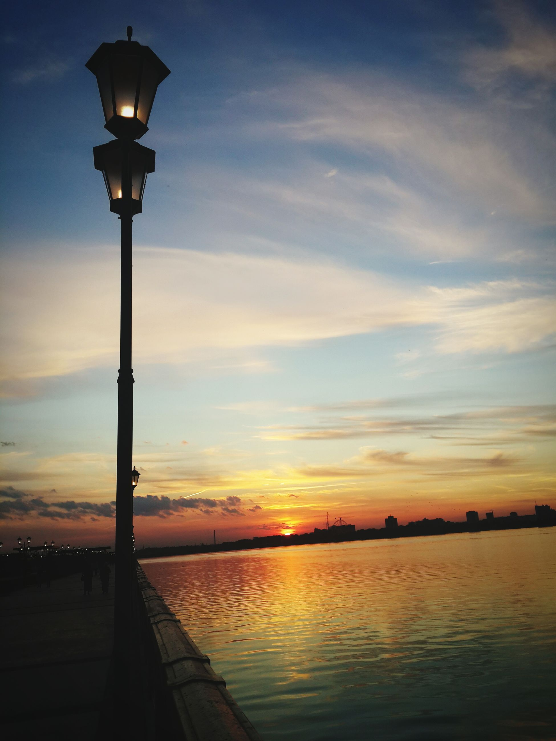 sunset, water, sky, street light, silhouette, scenics, tranquility, sea, tranquil scene, beauty in nature, reflection, lighting equipment, nature, cloud - sky, orange color, idyllic, sun, cloud, pier, outdoors