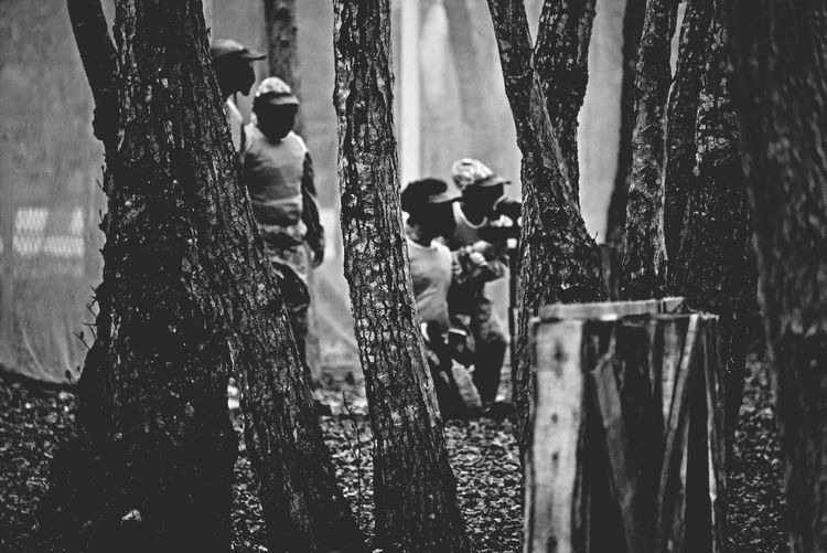 Man playing paintball in forest