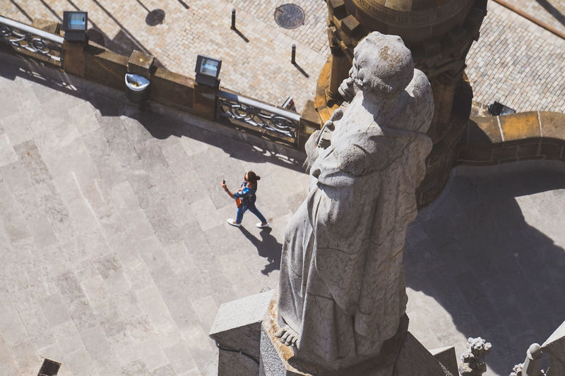 High Angle View Of Woman Walking On Footpath By Statue