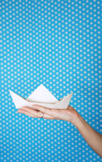 Cropped hand of woman holding paper boat against blue wall