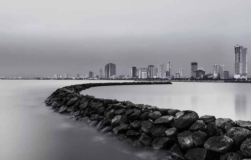 Rock Jetty Reaching Into The Sea With City In The Background