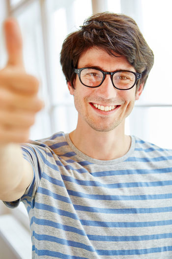 Portrait of smiling businessman showing thumbs up while sitting against window in office