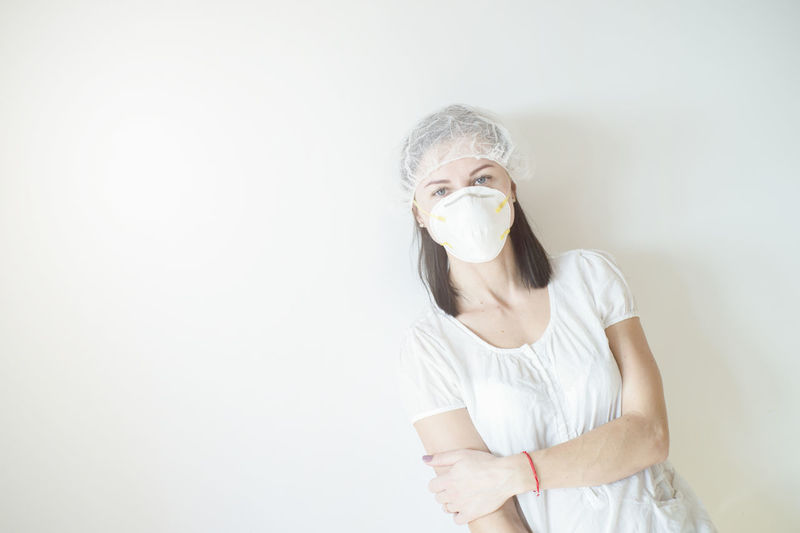 Portrait of woman wearing mask standing against white background
