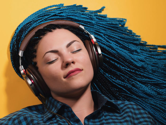 Beautiful young girl with african blue braids is listening to music with headphones and dancing. Woman on bright yellow background. Dyed Hair moves. African Earphones Headphones Listening To Music Music Afro Braids Afrohair Afrohairstyle Beautiful Woman Blue Hair Branch Caucasian Close-up Dyed Hair Headshot Hipster Indoors  Lifestyles Model One Person Real People Studio Shot Yellow Background Young Adult Young Women