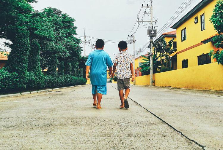Rear view of boys walking on street in city