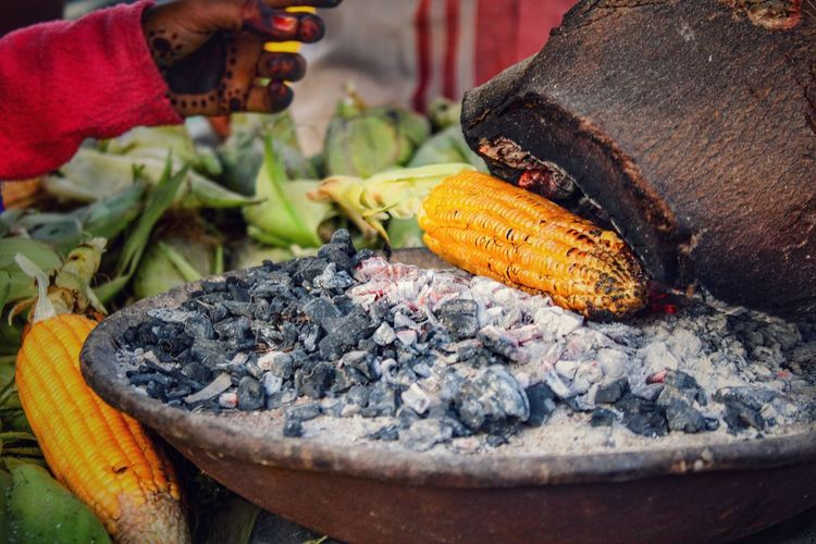 Close-up of person preparing corn on fire pit