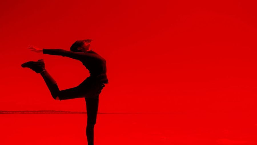 Stretching Woman Against Red Background