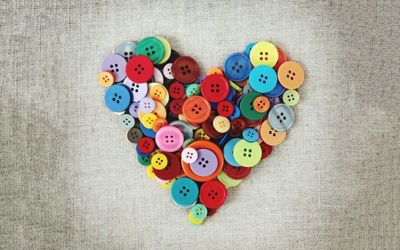 Directly above shot of heart shape made with colorful buttons on table