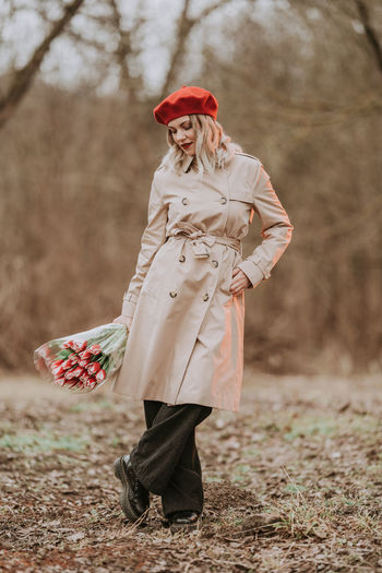 Full length of woman wearing trench coat holding bouquet standing in forest