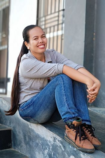Portrait of smiling woman sitting on retaining wall
