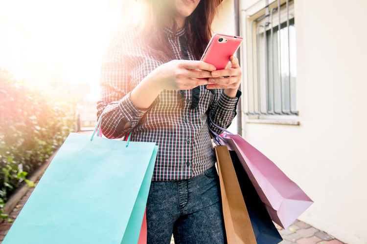 Young Woman With Shopping Using Mobile Phone
