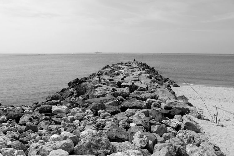 A Fisherman in the distance. Naturelovers Black & White EyeEm Black And White Blackandwhite EyeEm Nature Lover Blackandwhite Photography Bnw Eye4photography  EyeEm Best Shots EyeEmBestPics From My Point Of View Rock Pile Seaside Sky And Clouds Waves, Ocean, Nature Beachphotography EyeEm Gallery Taking Photos Portugal