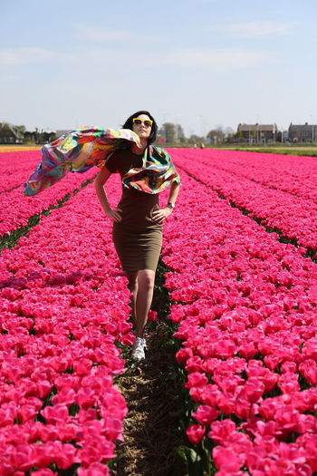 Full length portrait of woman standing by flowers