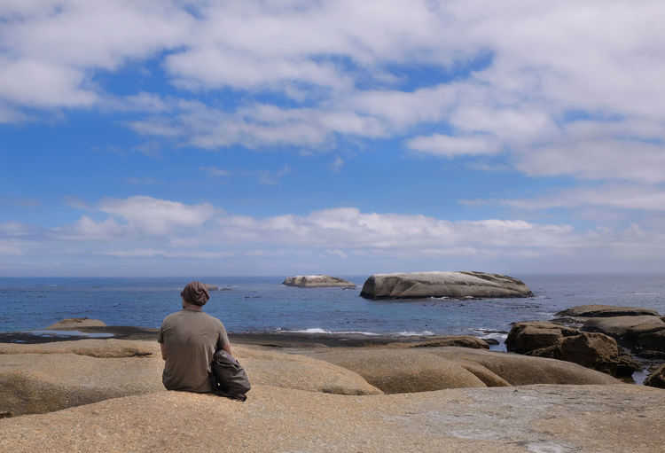 Rear view of man sitting on rocky shore against cloudy sky