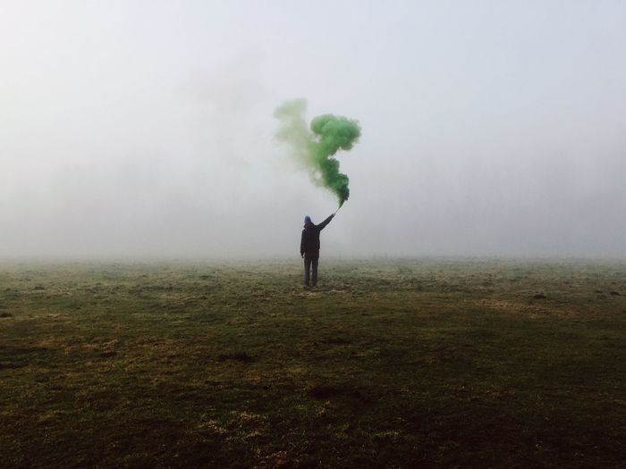 Rear View Of Man Holding Smoke Bomb On Field In Foggy Weather