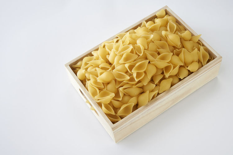 Close-up of raw pasta in crate against white background