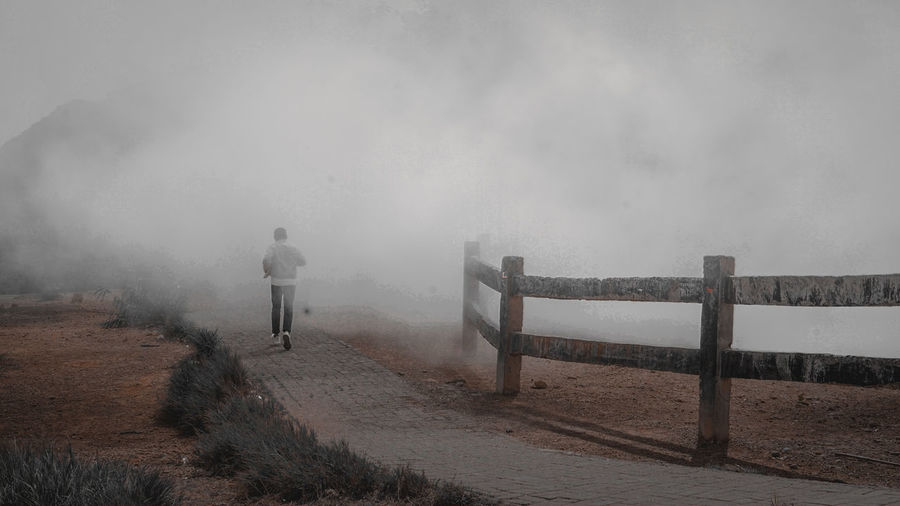 Rear view of man walking on foggy day