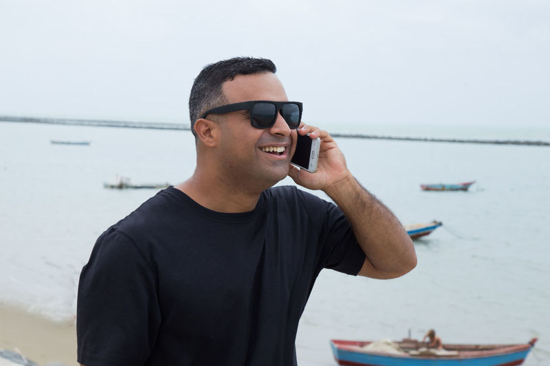 Man Wearing Sunglasses Using Mobile Phone By Sea Against Sky