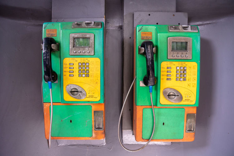Close-up of pay phones on wall