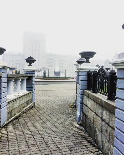 Architecture Building Exterior Built Structure City City Life Clear Sky Culture Day Foggy Fountain Leading Outdoors Paving Stone Railing River Sky The Way Forward Water