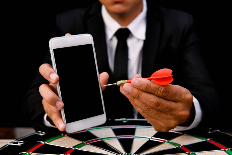 Midsection Of Businessman With Mobile Phone And Dart At Table Against Black Background