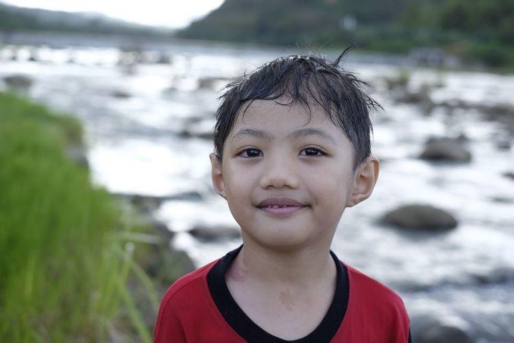 Portrait of smiling boy against river