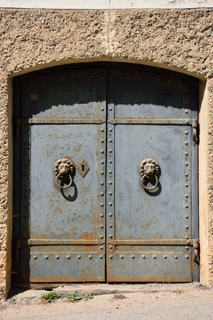 An old heavy iron door with lion motif handles. Some rust can be seen. Architecture Built Structure Close-up Closed Day Door Entrance Heavy Iron No People Old Outdoors Rust Rustic Rusty Safety Wood - Material Wooden