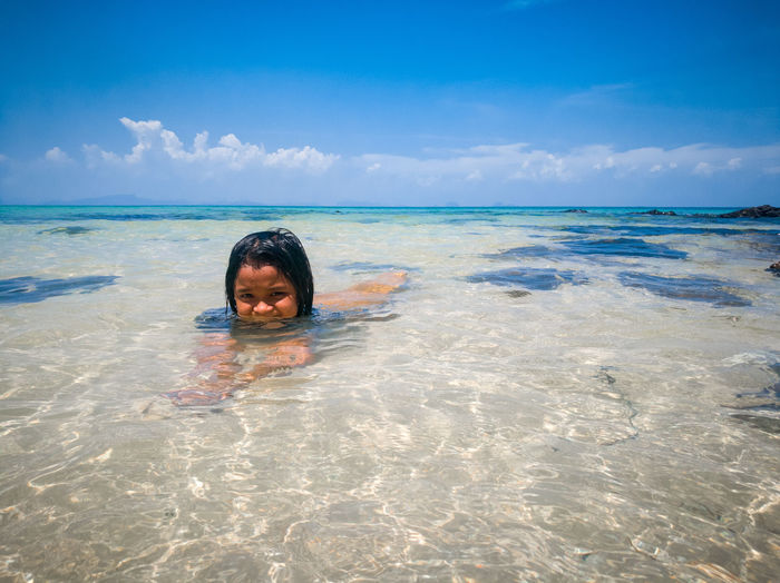 Portrait of girl swimming in sea against sky