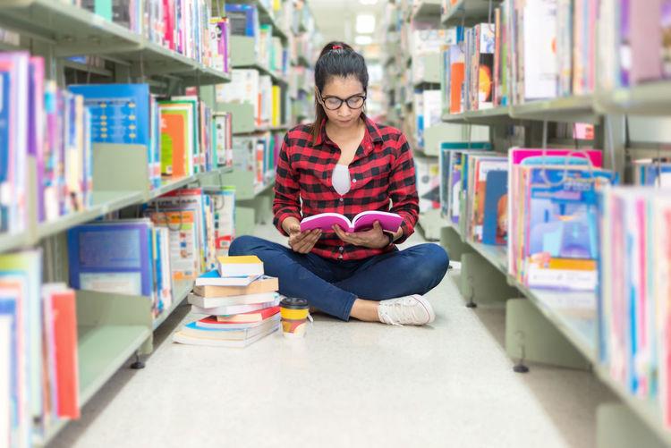 Woman reading book while sitting at bookshelf