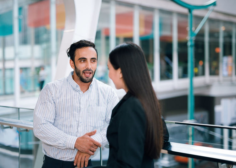 Businessman Talking With Colleague At Railing In Office