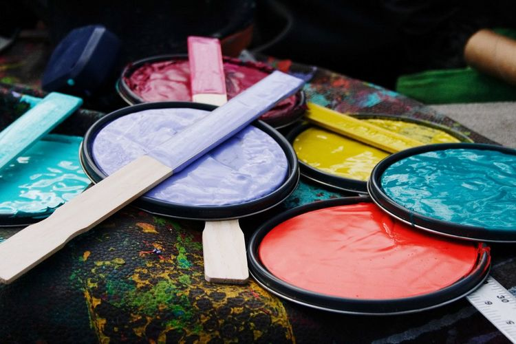 Close-up of paint can lids on table