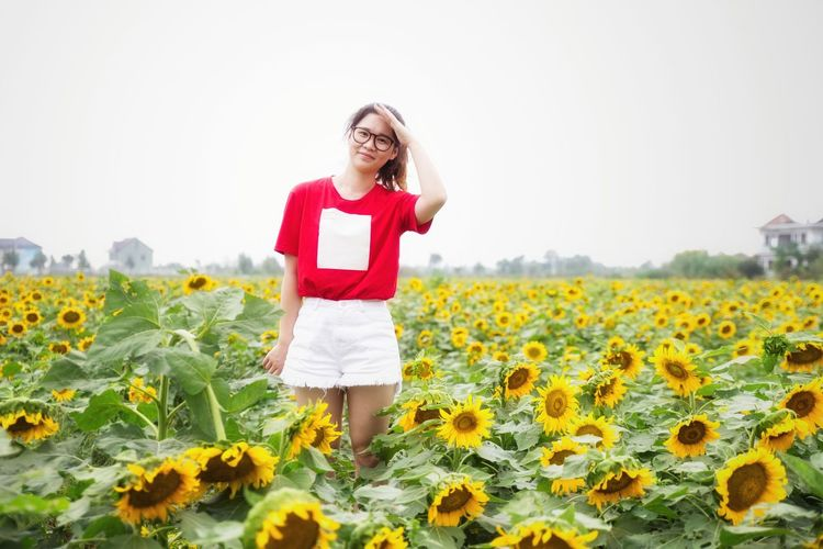 Portrait of young woman standing amidst sunflowers blooming on field against sky