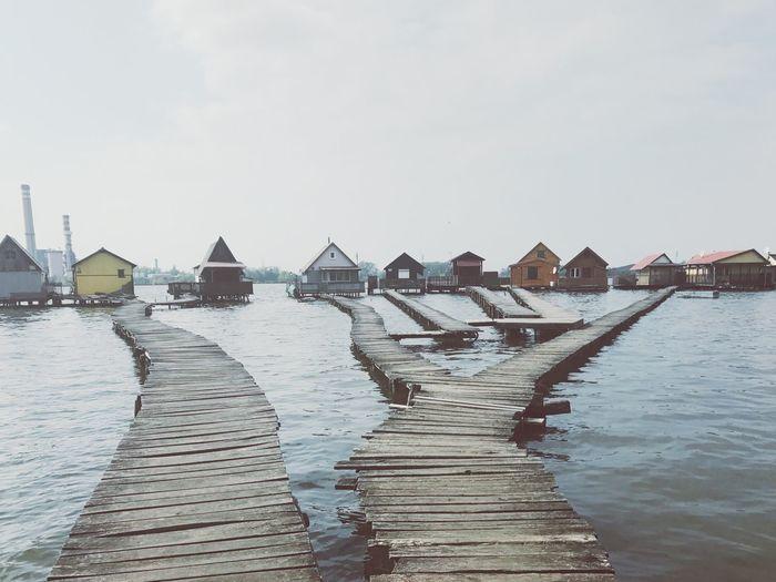 Houses on lake against sky