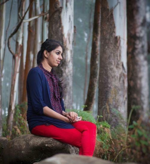 Side view of thoughtful young woman sitting on rock in forest