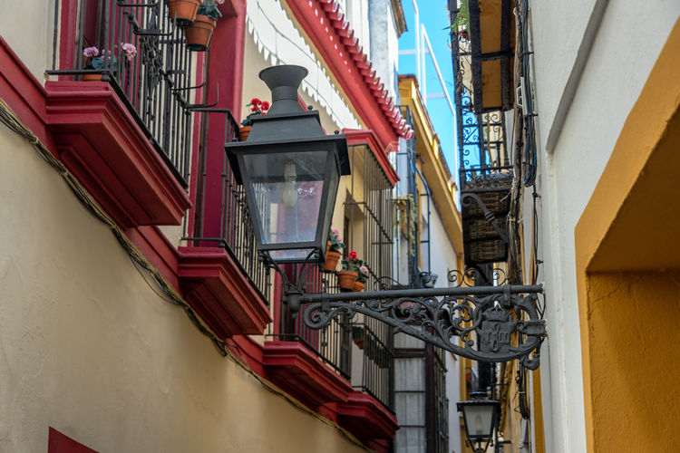 Old street light in a narrow street in Seville, Spain Sevilla Seville SPAIN Travel Destinations Travel Tourism Architecture Built Structure No People Europe Historic Andalucía Andalusia Street Light Streetlights Streetlight Red Lighting Equipment Building Building Exterior City Apartment Window Balcony