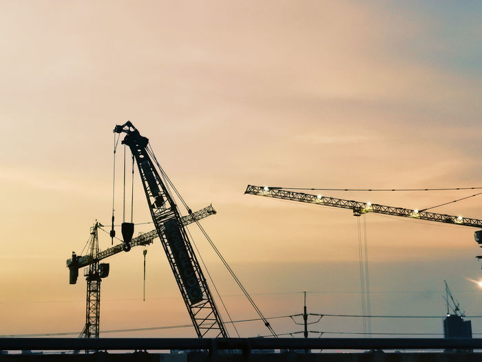 Low angle view of cranes at construction site against sky during sunset