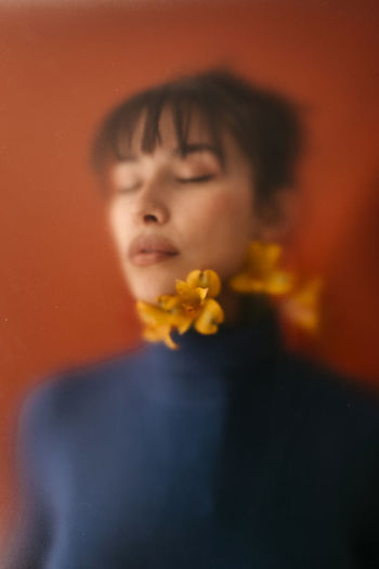 Close-up portrait of boy with orange flower