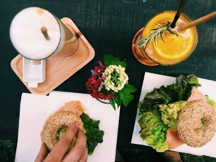 Sesame Bagel Filled With Smoked Salmon With Avocado Mash And Green Leafy Salad
