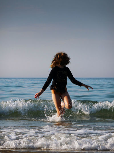 Rear view of woman on beach against sea against clear sky