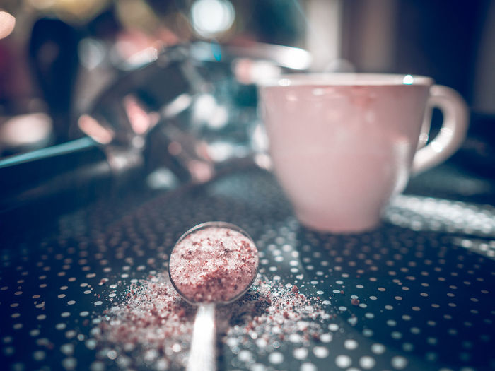 Liettel spoon with sugar an coffee cup in in background Sugar Spoon Espresso Equipment Food And Drink Indoors  Close-up Refreshment Drink Selective Focus No People Cup Table Food Household Equipment Freshness Focus On Foreground Kitchen Utensil Glass Crockery Pink Color Drinking Glass Still Life Wellbeing